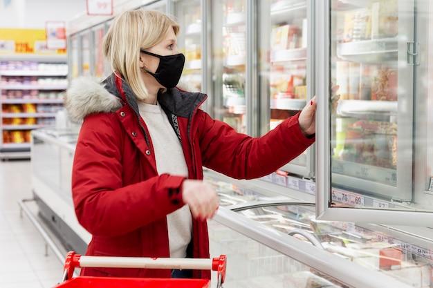 Giovane donna in una giacca rossa e una mascherina medica nera al supermercato nella sezione alimenti congelati.