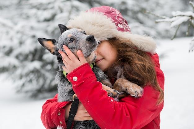 Giovane donna in giacca rossa e cappello di pelliccia che abbraccia heeler blu in inverno