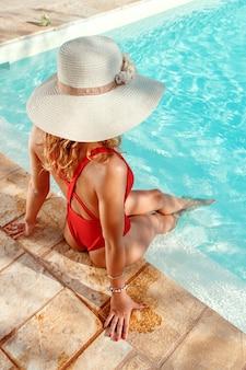 Giovane donna in costume da bagno intero rosso e cappello di paglia rilassarsi vicino a una piscina con le gambe in acqua