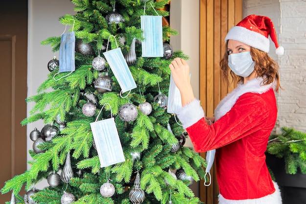 Una giovane donna in costume rosso da babbo natale decora l'albero di natale con maschere mediche. vacanza in quarantena. concetto di celebrare il nuovo anno e il natale sotto le restrizioni del coronavirus.