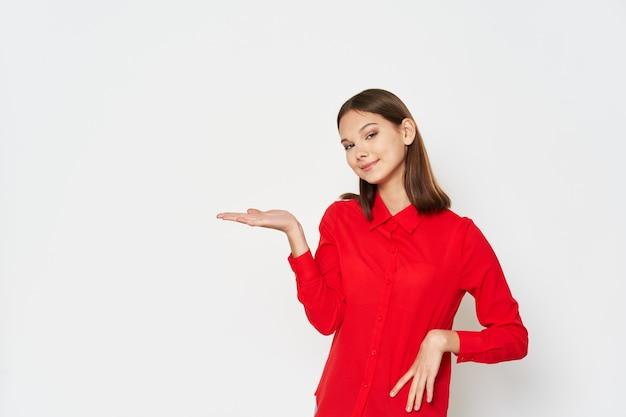 La giovane donna in una camicia rossa mostra con la sua mano al lato su uno spazio leggero della copia del fondo