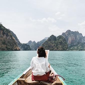 Giovane donna in gonna rossa e camicetta bianca che si siede sulla barca di legno che guarda alle isole esotiche e tropicali con le rocce