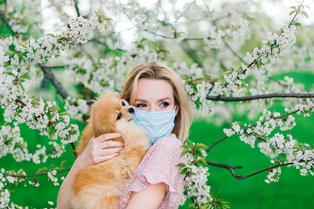 Giovane donna e spitz rosso con una maschera medica sul viso sulla natura in una giornata di primavera