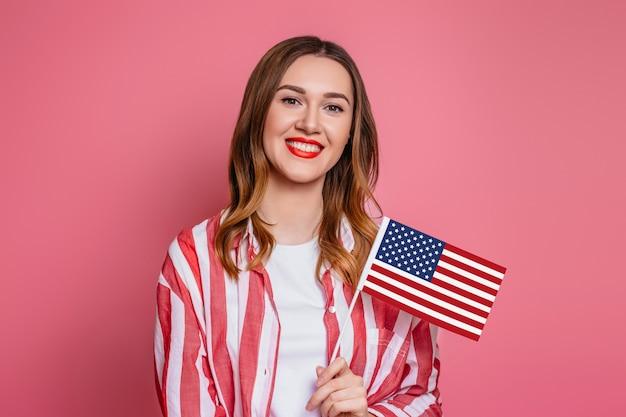 La giovane donna in una camicia a strisce rossa con rossetto rosso tiene la bandiera americana ed i sorrisi isolati sopra spazio rosa, il quarto della festa dell'indipendenza di luglio