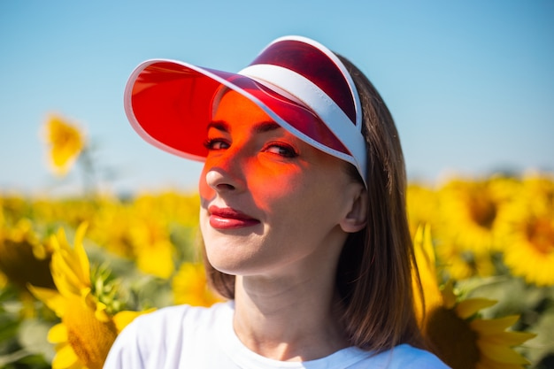 Giovane donna in visiera parasole rossa e maglietta bianca sul campo di girasoli.