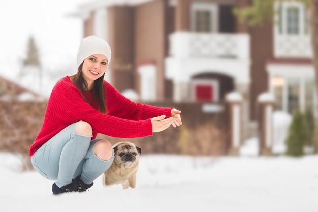 Giovane donna in un maglione rosso jeans strappati blu cappello bianco con un cane carlino