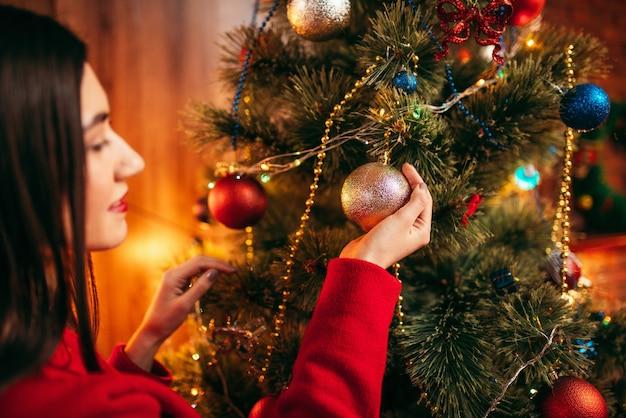 La giovane donna in maglione rosso decora l'albero di natale