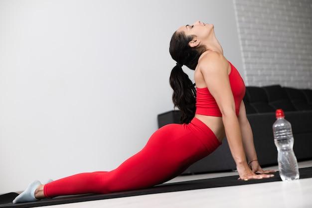Giovane donna in tuta sportiva rossa facendo esercizio o yoga a casa. vista dal basso della ragazza magra ben costruita che allunga la schiena sdraiandosi sulla stuoia e tenendosi con le mani. bottiglia d'acqua inoltre.