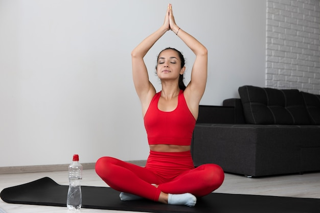 Giovane donna in tuta rossa facendo esercizio o yoga a casa