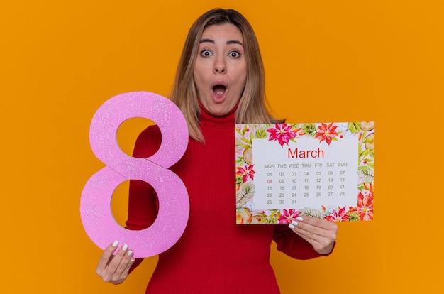 Giovane donna in dolcevita rosso che tiene il calendario cartaceo del mese di marzo e il numero otto