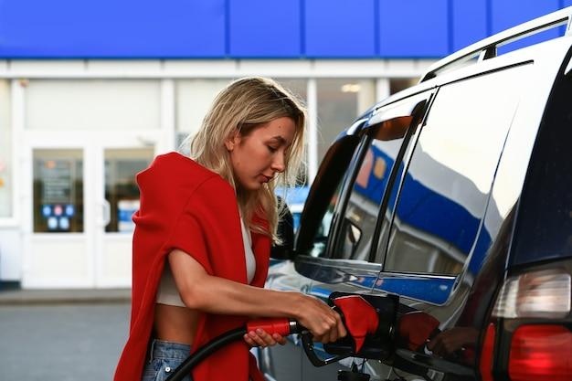 Giovane donna che fa rifornimento di carburante alla sua auto in una stazione di servizio. studentessa bionda attraente. messa a fuoco selettiva sfocata