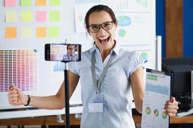 Giovane donna che si rallegra e tiene in mano i documenti davanti alla fotocamera del telefono cellulare su treppiede. concetto di corso di formazione aziendale online