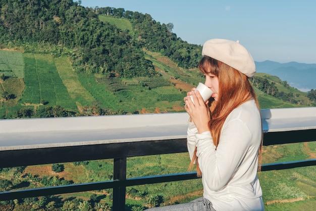 Giovane donna che si rilassa e che beve caffè sul caffè di montagna