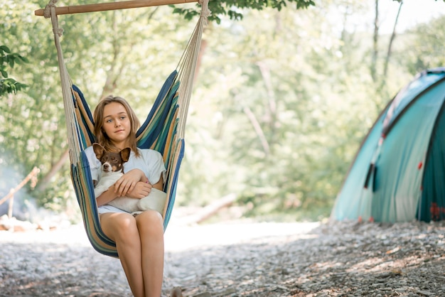 Una giovane donna che si rilassa su un'amaca con il suo cane. ragazza che riposa su un'amaca nel bosco, in campeggio. stile di vita sano nella foresta.