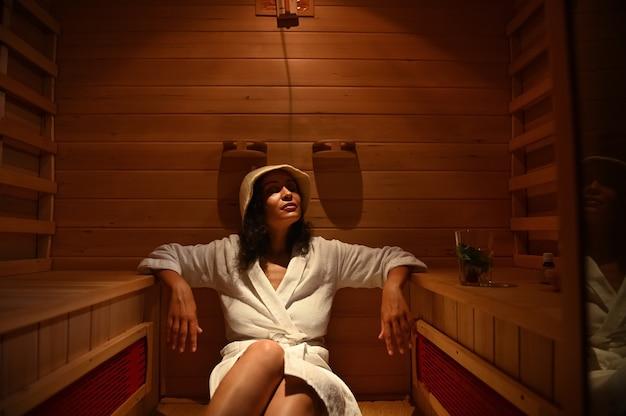 Giovane donna che si rilassa nella sauna a infrarossi durante una procedura presso il centro termale. cura del corpo