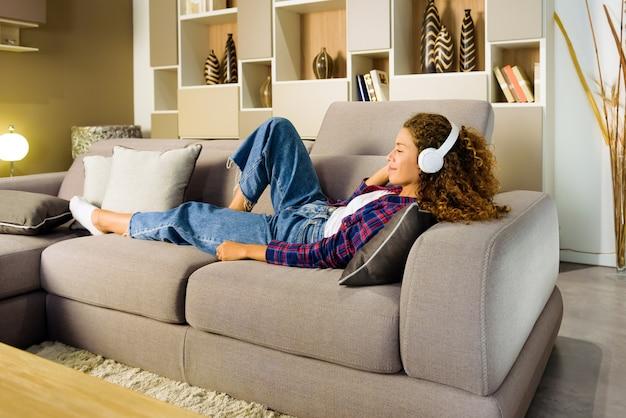 Giovane donna che si distende ascoltando musica a casa sdraiata su un comfoin il soggiorno con un sorriso di piacere