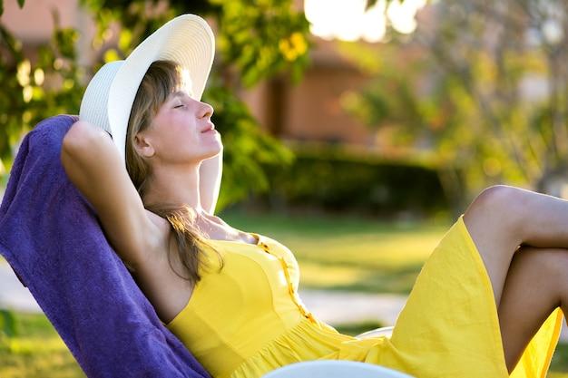 Giovane donna che si rilassa all'aperto il giorno di estate pieno di sole. felice signora sdraiata