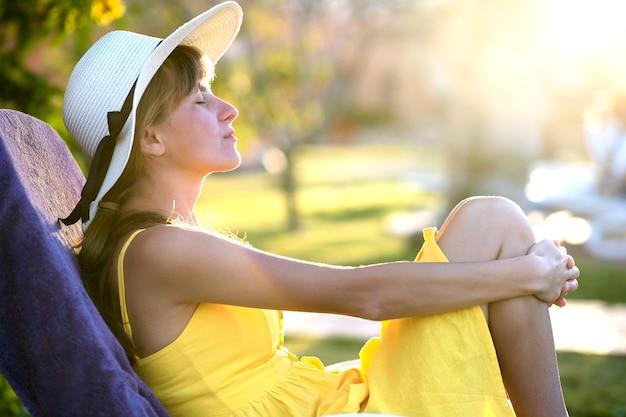 Giovane donna che si distende all'aperto sulla soleggiata giornata estiva.