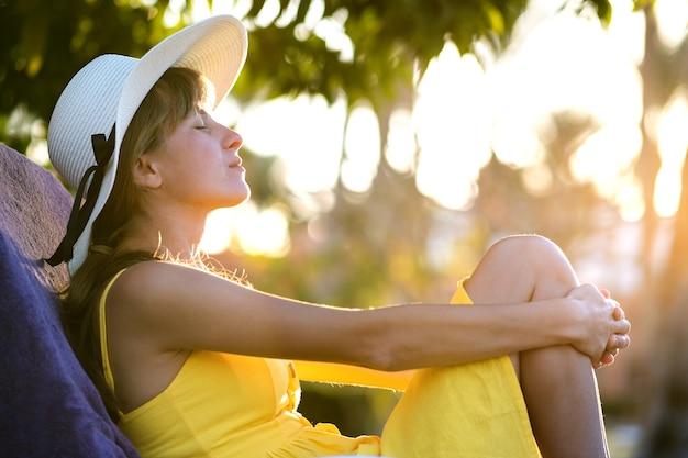 Giovane donna che si distende all'aperto sulla soleggiata giornata estiva