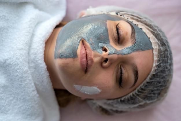 Giovane donna in un momento di relax a spa, sdraiata a letto con maschera facciale