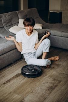 Giovane donna che si rilassa mentre il robot pulisce il pavimento con l'aspirapolvere