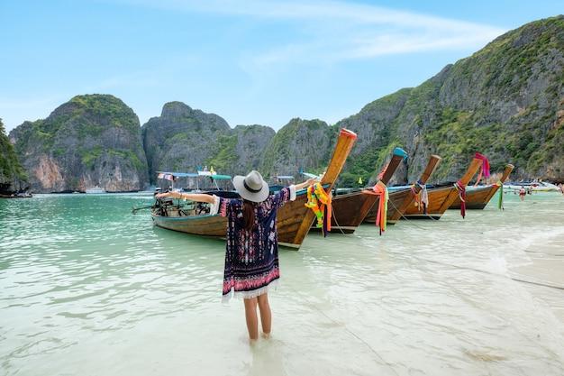Giovane donna che si rilassa sulla barca a coda lunga di legno nella baia di maya
