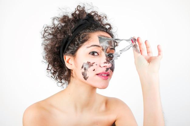 Giovane donna che rimuove la maschera di protezione nera contro fondo bianco
