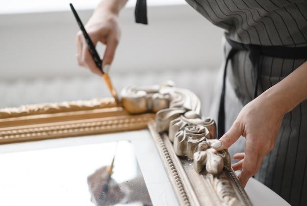 La giovane donna ripara la cornice per uno specchio o un'immagine