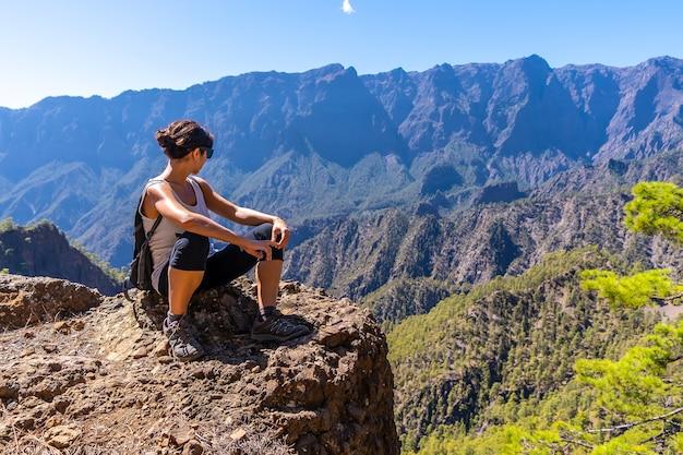 Una giovane donna in appoggio dopo il trekking sulla sommità di la cumbrecita seduto nel punto di vista naturale guardando le montagne della caldera de taburiente, isola di la palma, isole canarie, spagna
