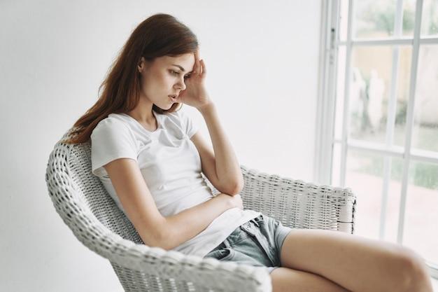 Giovane donna che riposa sulla poltrona a casa vicino alla finestra