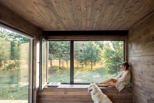 Giovane donna che riposa in una bella casa di campagna o in un hotel, seduta sul davanzale della finestra con vista sulla pineta e un grosso cane bianco si siede vicino. concetto di solitudine e ricreazione sulla natura con pet
