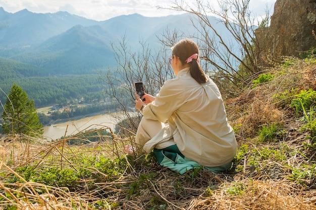 Giovane donna che riposa in montagna ragazza che fa un'escursione con gli zaini su un bellissimo sentiero roccioso concetto di viaggio e avventura locale