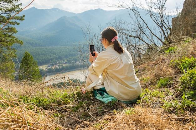 Giovane donna che riposa in montagna ragazza che fa un'escursione con gli zaini su un bellissimo sentiero roccioso