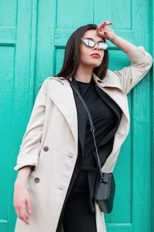 Giovane donna in blazer retrò in t-shirt nera alla moda in trench alla moda primaverile riposa vicino alla porta turchese in legno brillante vintage sulla strada. ragazza di moda in primo piano abbigliamento casual. stile giovanile.