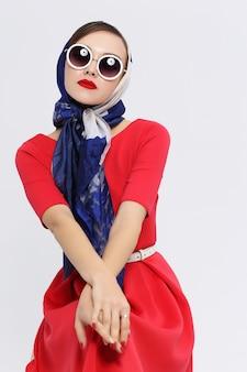 Giovane donna in stile retrò con occhiali da sole e sciarpa di seta. donna retrò di moda stile anni sessanta.