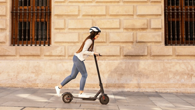 La giovane donna guida in uno scooter elettrico in città
