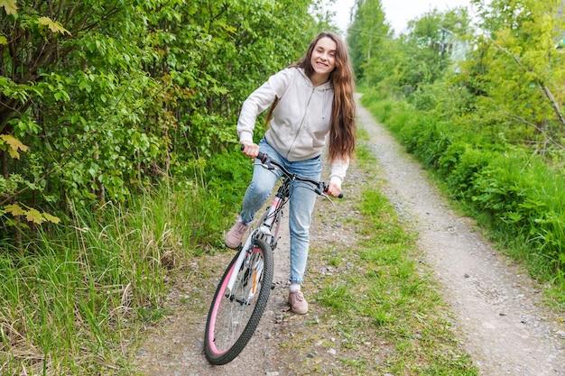 Bicicletta di guida della giovane donna nel parco della città di estate all'aperto. persone attive. la ragazza dei pantaloni a vita bassa si rilassa e la bici del pilota. andare in bicicletta al lavoro al giorno d'estate. concetto di stile di vita in bicicletta ed ecologia