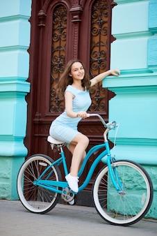 Giovane donna che guida bicicletta blu all'aperto
