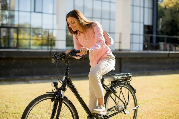 Giovane donna in sella a bici in ambiente urbano