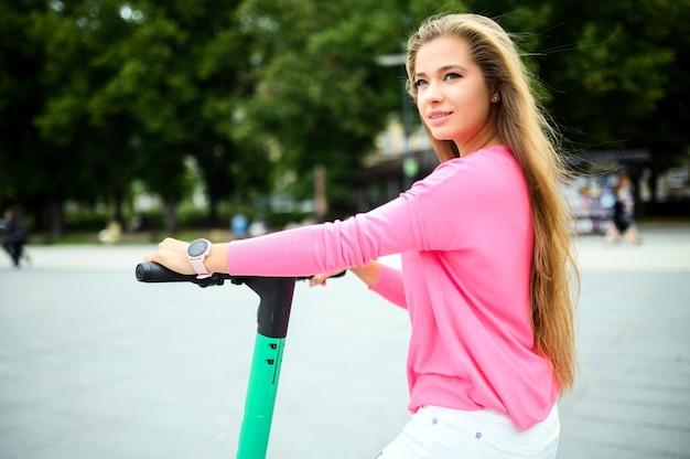Giovane donna in sella a uno scooter elettrico in città