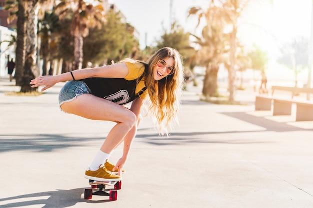 Giovane donna a cavallo di un lungo skateboard all'aperto in stile california