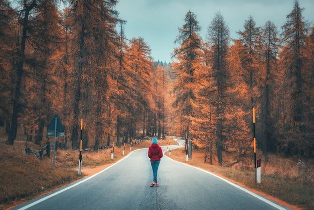 Giovane donna sulla strada nella foresta di autunno al tramonto