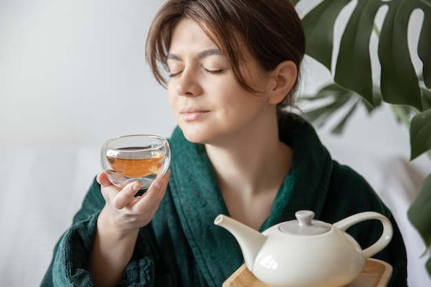 Giovane donna in accappatoio che si gode il concetto di tè di trattamenti termali e relax