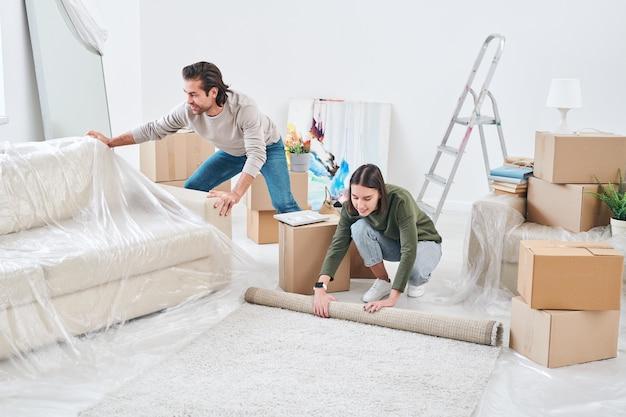 Giovane donna che rotola tappeto sul pavimento mentre suo marito mette il cellophane sul divano prima della riparazione della loro nuova casa o appartamento