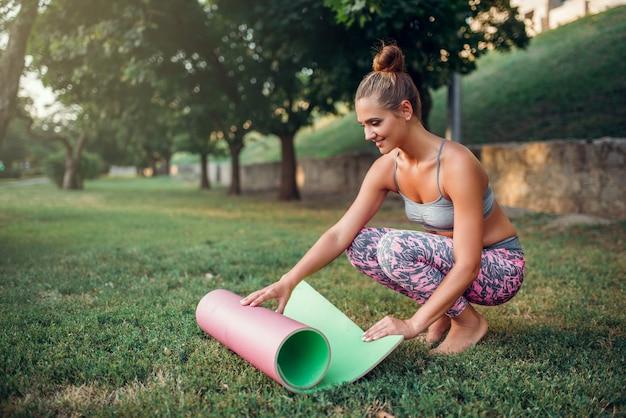 Stuoia di yoga di rotolamento della giovane donna nel parco