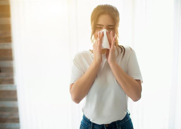 Giovane donna in camera. soffiarsi il naso usando un tessuto bianco. malato malato stand alone alla finestra.