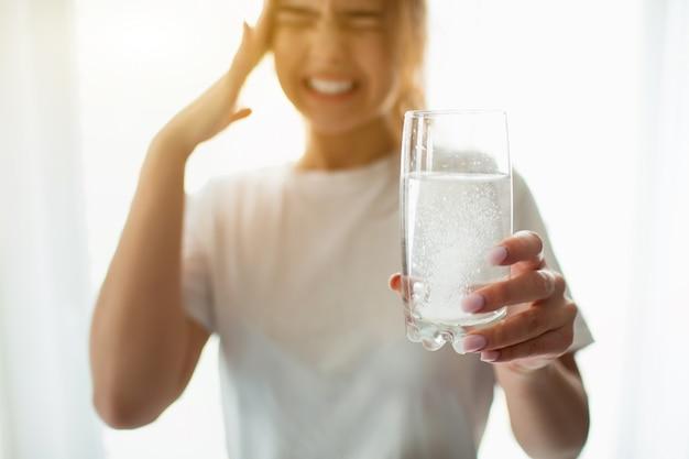 Giovane donna in camera. soffre di forti mal di testa o dolore. tieni il bicchiere con una compressa effervescente. postumi di una sbornia o mal di testa.