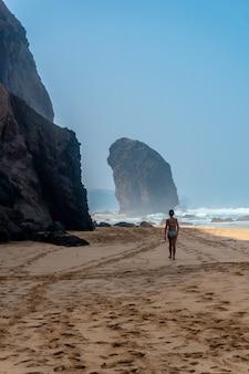 Una giovane donna nel roque del moro della spiaggia di cofete del parco naturale di jandia, barlovento, a sud di fuerteventura, isole canarie. spagna