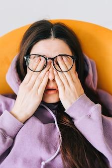 La giovane donna si strofina gli occhi dopo aver usato gli occhiali nella parte anteriore del laptop. il dolore agli occhi o il concetto di affaticamento.