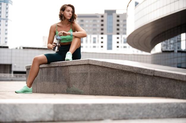 Corridore della giovane donna che riposa dopo la sessione di allenamento sulla strada urbana